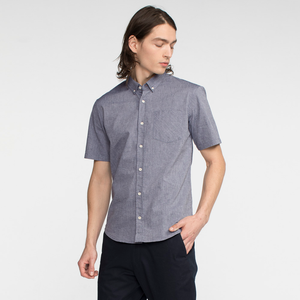 Model side facing wearing a short sleeve, chambray, button up shirt.