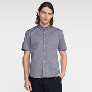 Model front facing wearing a short sleeve, chambray, button up shirt.