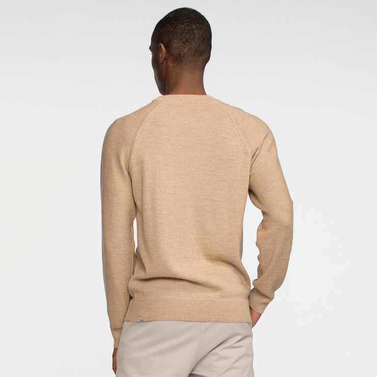 Model back facing wearing a natural colored, raglan sleeved, sweater.