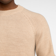 Zoomed in view of raglan sleeve on a model wearing a natural colored alpaca sweater.
