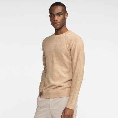 Model side facing wearing a natural colored alpaca, raglan sleeved sweater.