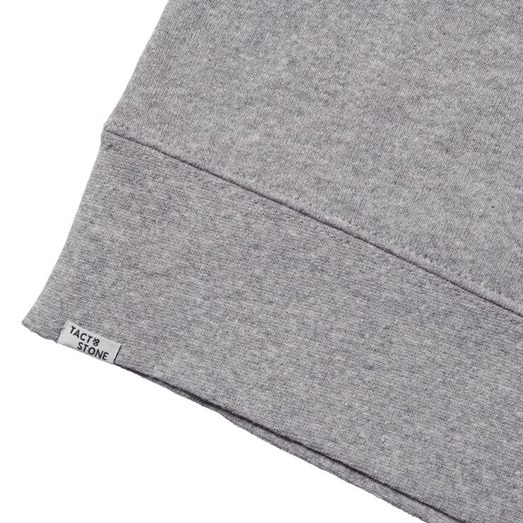 Zoomed in view of the back hem of a hooded heather grey sweatshirt, focusing on Tact & Stone label.