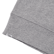 Zoomed in flat lay of back hem showing Tact & Stone label on heather grey sweatshirt.