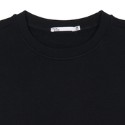 Zoomed in flat lay view of the collar and neck label of a crewneck, black sweatshirt.