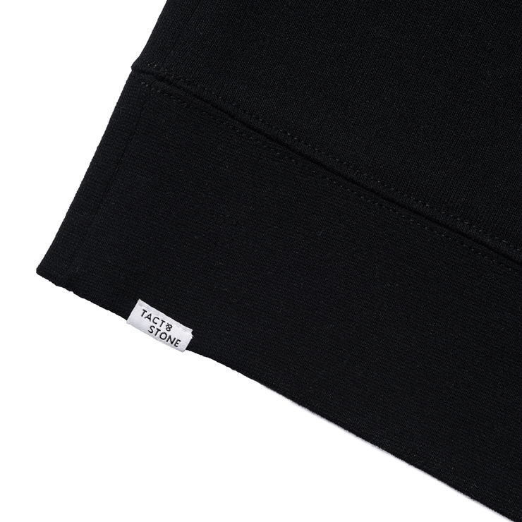 Zoomed in flat lay of back hem of black hooded sweatshirt. Focused on the Tact & Stone label.