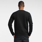 Model back facing wearing a black, sustainable, crew neck sweatshirt.