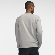 model facing back wearing sustainable heather grey crewneck sweatshirt.
