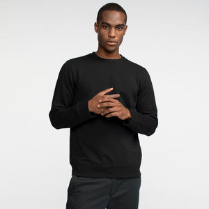 Model front facing wearing a black, sustainable, crewneck sweatshirt.