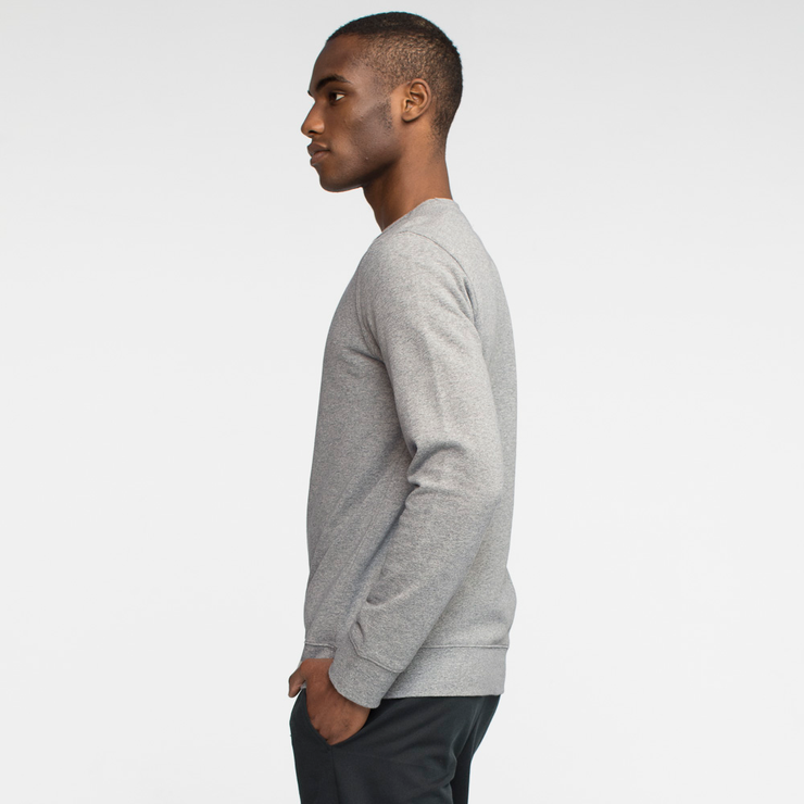 Model side facing wearing heather grey crew neck sweatshirt.