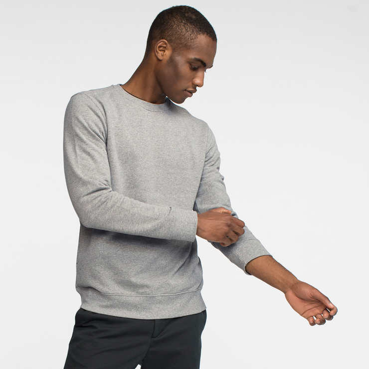 Model side facing wearing heather grey crewneck sweatshirt, pulling up his left arm sleeve.