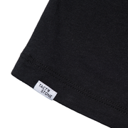 Zoomed in view of back hem of black tee shirt with Tact & Stone label. Made with organic cotton and recycled polyester.