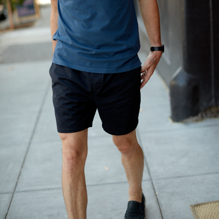 Model front facing, walking on the sidewalk. The shot is focused on black colored shorts that sit just above the knee.