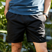 Front facing model wearing black colored, drawstring waistband shorts.