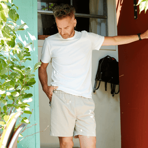 Model standing in a doorway wearing khaki colored shorts with a drawstring waistband.