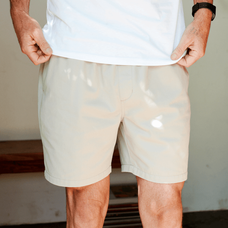 Model front facing, focused on khaki colored shorts.