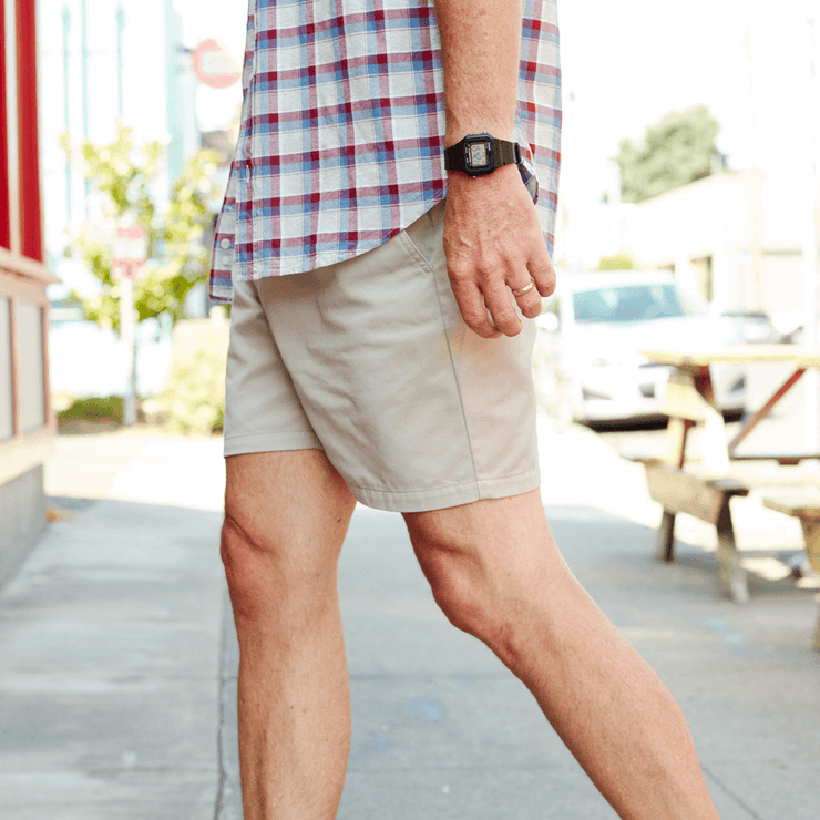 Model side facing wearing khaki colored shorts.