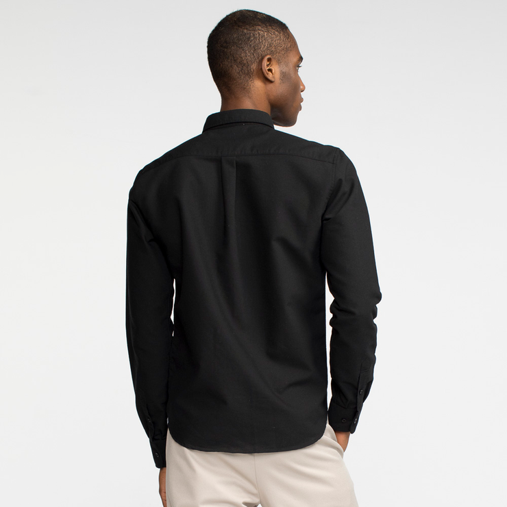 Model back facing wearing a long sleeve, black oxford shirt.