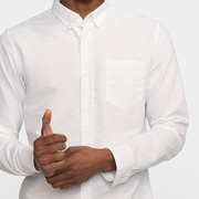 Zoomed in view of a white, long sleeve, oxford shirt, on a model.