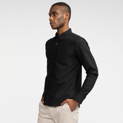 Model side facing wearing a long sleeve, black oxford shirt.