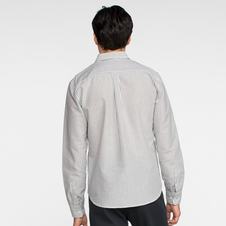 Model facing back wearing a long sleeve, striped oxford shirt.