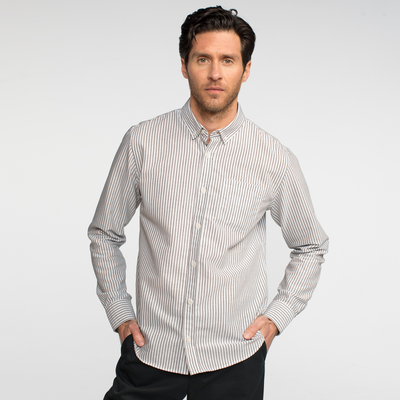 Model front facing wearing a long sleeve, striped oxford shirt.