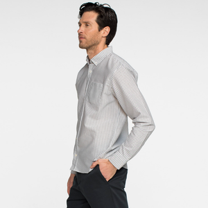 Model side facing wearing a long sleeve, striped, oxford shirt.