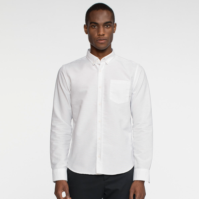Model facing front wearing a long sleeve, white, oxford shirt.