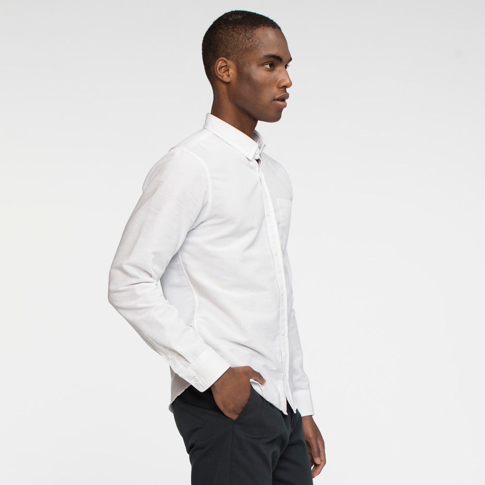 Model side facing wearing a long sleeve, white, oxford shirt.