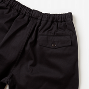 Zoomed in flat lay of black, drawstring waistband shorts. Focused on shorts back pocket and button closure.