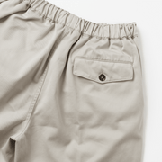 Zoomed in flat lay of khaki colored shorts, focusing on the back right pocket of the shorts and the button closure.