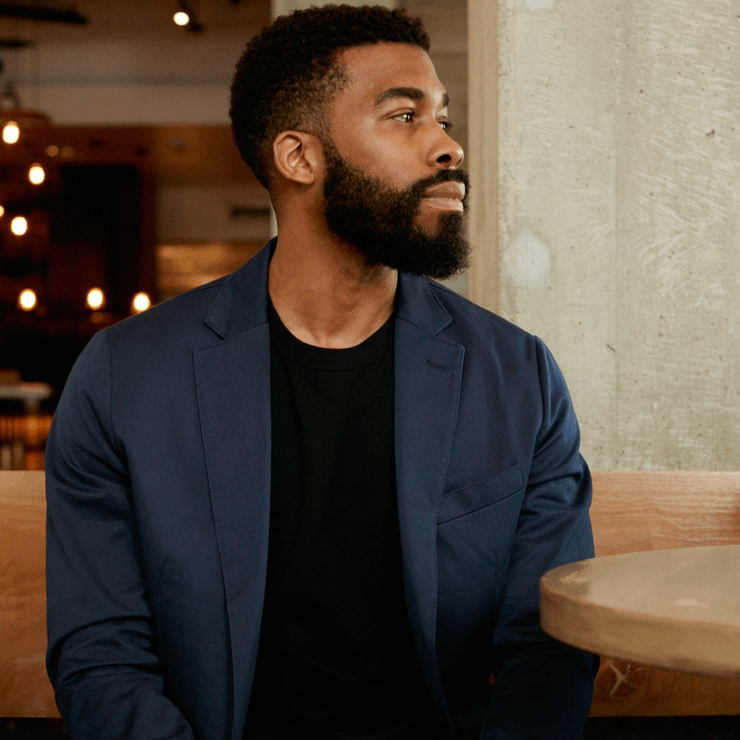 Model in a restaurant wearing a sustainable navy blazer, looking to his left