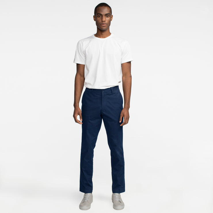 Model front facing highlighting navy colored chinos. Sustainable, performance chinos.