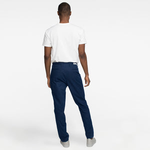 Model back view highlighting performance, sustainable navy chinos.