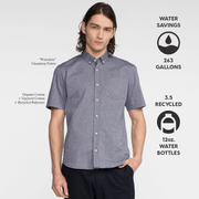 Model front facing wearing a short sleeve, chambray, button up shirt. Iconography explaining sustainability benefits of the shirt.