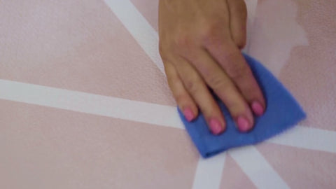 A ladies hand with pink nail varnish cleaning milk from a Toddlekind Vintage Nude pink playmat