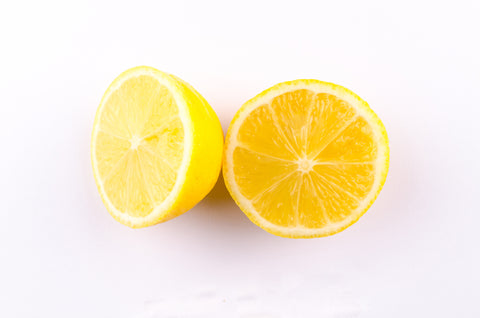 A lemon cut in half on a white background