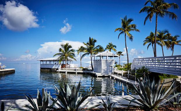 This is the Coming Soon image for Casa Morada, a boutique hotel in Islamorada. The picture shows the hotel's private island surrounded by water, with blue skies, palm trees, and a footbridge which leads to a swimming pool and cabana.