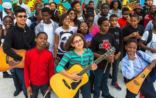 Boys and girls of various ages and ethnicities gather outside with musical instruments during a Guitars Over Guns event to promote musical learning