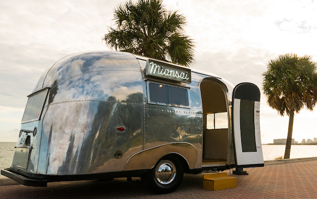 This is a Coming Soon image for Miansai, a jewelry company based in Miami. The picture shows a polished silver Airstream trailer aside the ocean with palm trees swaying overhead.