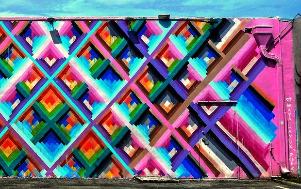 This photograph shows the graffiti painted walls of a warehouse in the Wynwood Arts District, the paint being vivid pinks, blues, reds and purples