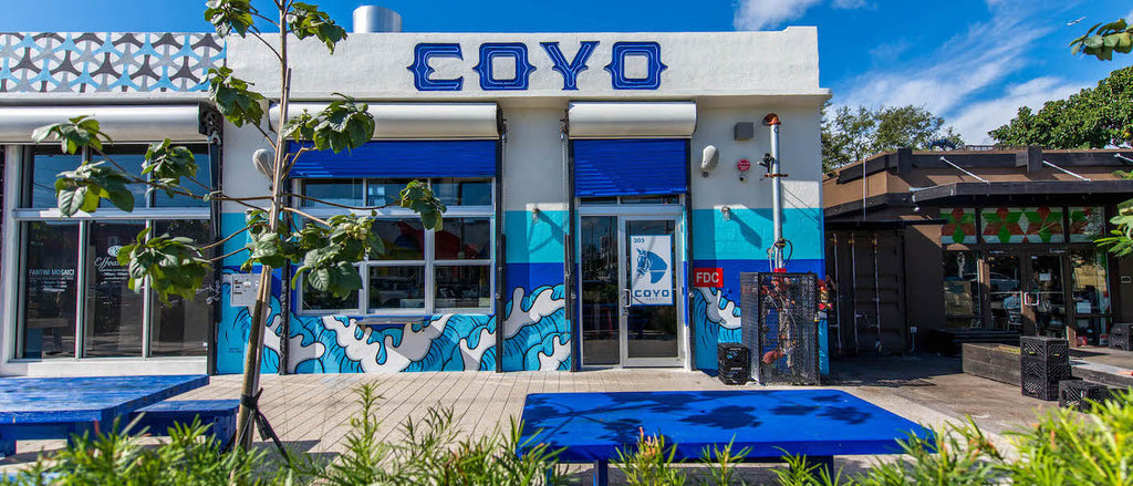 The exterior of Coyo Taco in the arts neighborhood of Wynwood shows communal dining picnic tables and vivid Mexican blue and green colors painted on the walls