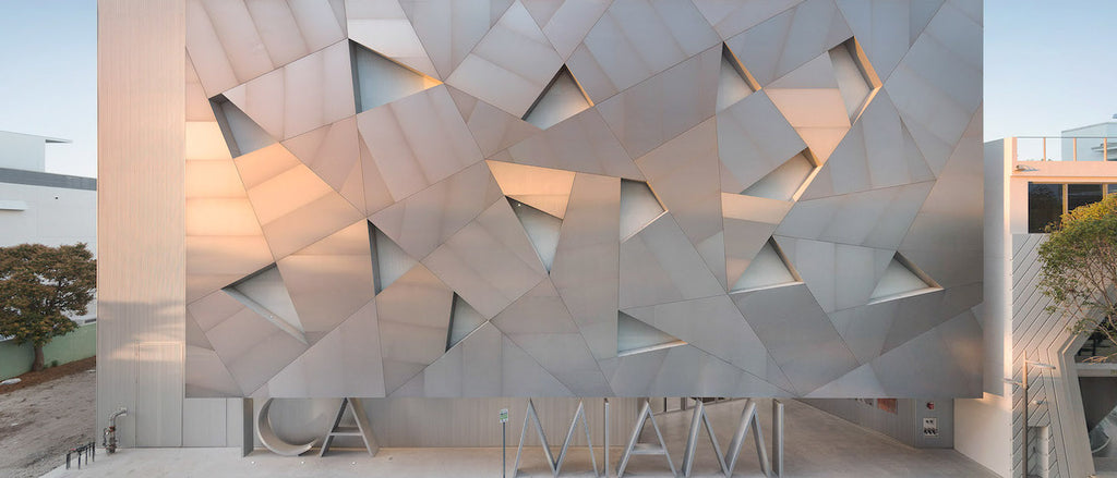 The rectangular exterior of Institute of Contemporary Art in Miami's Design District features geometrically-cut, shiny aluminum panels and a large ICA MIAMI lettering at street level
