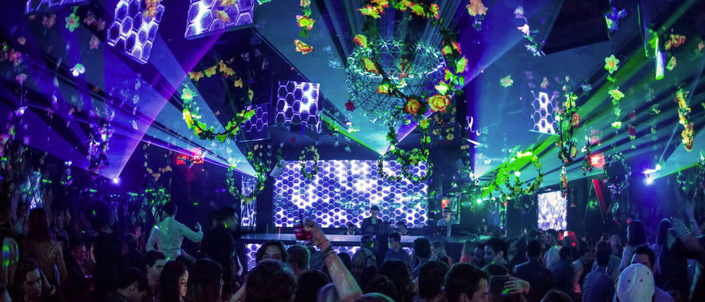 At Wall nightclub, a crowd of dancing people move to the rhythms of dance music while fantastical blue, green and purple lighting illuminates the DJ booth