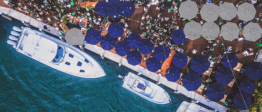 An overhead photograph of The Wharf taken from a drone shows many large boats parked along a seawall as customers socialize under large blue umbrellas
