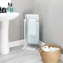 Load image into Gallery viewer, Latest mdesign tall modern metal and bamboo wood towel rack holder 2 tier organizer for bathroom storage and organization next to tub or shower holds bath hand towels washcloths white natural