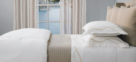 white bedding with textured pillow shams and a coverlet