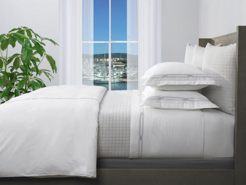 white bedding set in a bedroom with an ocean view