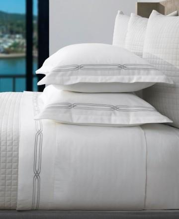 white bedding with a quilted coverlet and shams