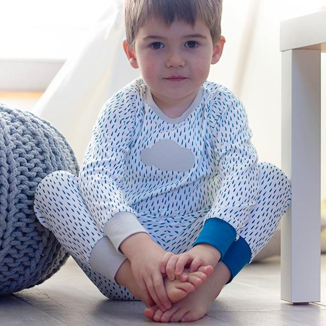 Boy sitting wearing rain cloud unisex kids pyjamas. 100% organic cotton.