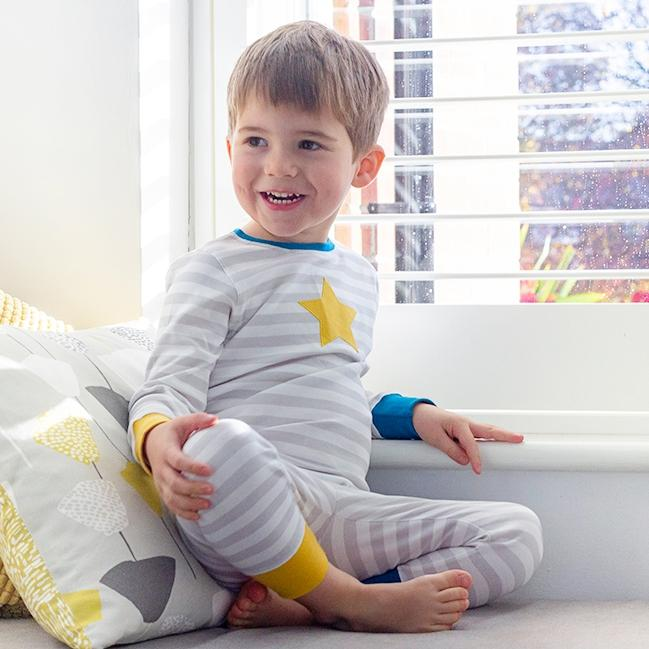 Boy sitting by window in grey and blue stripe organic cotton pyjamas with yellow star.